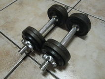 Training Weights. Black iron cast dumbbell training weights, 2x 7.5Kg on a textured tile background Stock Image