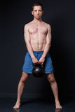 Training with weights. Strong man holding a kettlebell between y Royalty Free Stock Images