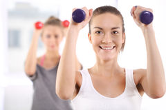 Training with weights, two young women in the gym Royalty Free Stock Photography