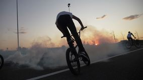 Training of young bikers riding and practicing acrobatic techniques on cycling circuit outdoor at the sunset with smoke -. Training of young bikers riding and stock video