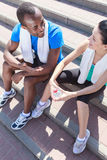 After the training. Young interracial couplesitting at stairs an Royalty Free Stock Photo