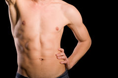 Training young man torso. Trained young man naked torso on a black background Stock Images