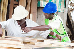 Training of a young student in carpentry. Royalty Free Stock Photos