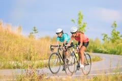 Trainingszyklus der zwei weiblichen kaukasischen Sportlerinnen, die s reiten Stockfotos