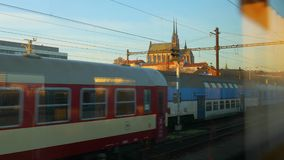 Trains arriving in town. BRNO, CZECH REPUBLIC - NOVEMBER 17, 2017: Trains arriving at Brno, passing by another train viewed from the window. Petrov Cathedral in stock video footage