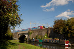 Trains and boats. An intercity train crosses a bridge over a canal barge Royalty Free Stock Photography