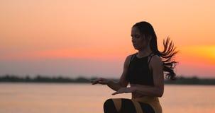 Trains de femme fonctionnant sur place au coucher du soleil sur la plage près de l'étang Formation ? l'aube banque de vidéos