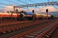 Trains de fret avec des véhicules de réservoir de carburant dans le coucher du soleil Image libre de droits