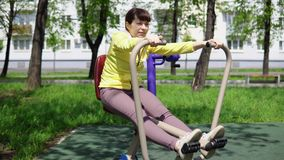 Trains de jeune femme sur les simulateurs stationnaires en plein air banque de vidéos