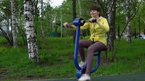 Trains de jeune femme sur les simulateurs stationnaires en plein air clips vidéos