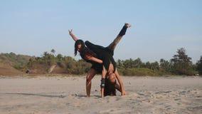 Trains de maman une fille de l'adolescence pour exécuter l'élément acrobatique sur la plage banque de vidéos