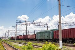 Trains with goods and freight cars are on the railway. Trains with freight cars and freight cars stand on the railway side view, wires over the cars and railroad royalty free stock photos