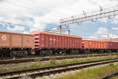 Trains with goods and freight cars are on the railway. Trains with freight cars and freight cars stand on the railway side view, wires over the cars and railroad royalty free stock photo