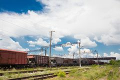 Trains with goods and freight cars are on the railway. Trains with freight cars and freight cars stand on the railway side view, wires over the cars and railroad stock photo