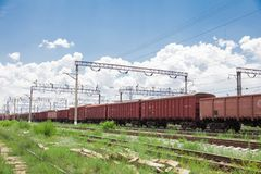 Trains with goods and freight cars are on the railway. Trains with freight cars and freight cars stand on the railway side view, wires over the cars and railroad stock photos