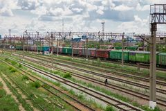 Trains with goods and freight cars are on the railway. Trains with freight cars and freight cars stand on the railway side view, wires over the cars and railroad stock images