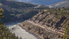 Trains Laboring through the Fraser Canyon in Britsh Columbia. Long trains laboring their way through the Fraser Canyon. The trains are generally 2 km or 1.25 Royalty Free Stock Image
