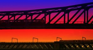 Trains that pass in the night. Sunset Silhouette as two Trains pass each other going in opposite directions on Bridges over the River Tyne in Newcastle, England Stock Images