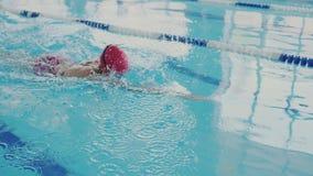 Trains professionnels de nageur dans la piscine Elle nage comme un rampement et fait habilement une course avec ses mains Fuselag banque de vidéos