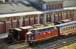 Trains on the railway station. Tilt-shift photo. Perfect models of the older (steam) and newer (diesel) locomotives and passenger trains wait on the railway Royalty Free Stock Images