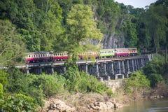 Trains thaïlandais fonctionnant sur la rivière de kwai de passage à niveau de la mort dans Kanchanaburi image libre de droits