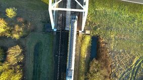 Trains top view. Straight down top shot of a train crossing a bridge over the road stock footage