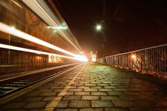 Trainstation at night. Lights and stripes of a passing train Stock Image