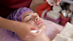 Traitement anti-vieillissement de visage avec le masque protecteur d'une femme Le cosmetologist met un gel de hydrater sur le vis banque de vidéos
