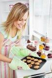 Traitement au four avec du charme de femme dans la cuisine Image libre de droits