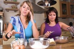 Traitement au four de deux filles dans la cuisine Photographie stock