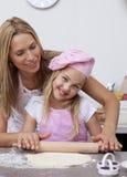 Traitement au four heureux de mère et de descendant dans la cuisine Photos libres de droits