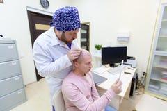 Traitement de calvitie Douleur patiente de la perte des cheveux en consultation avec un docteur Pr?paration pour la greffe de che photo stock