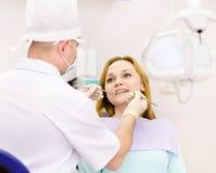 Traitement de dentiste dents de filles dans le bureau dentaire Image libre de droits