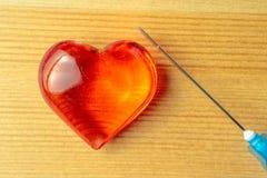 Traitement de l'amour, coeur de verre pour des travaux du ménage et seringue Photographie stock libre de droits