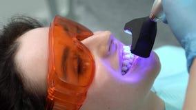 Traitement des dents de la jolie femme dans la clinique dentaire banque de vidéos