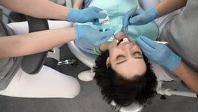 Traitement des dents de la jolie femme dans la clinique dentaire clips vidéos