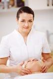 Traitement facial avec le thérapeute de massage pendant Photos stock