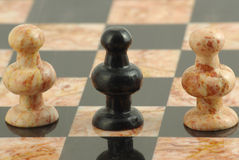 The traitor pawn in chess. Black pawn between tow white peons Stock Photography