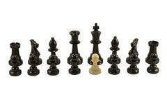 The traitor. White pawn standing alongside the chess black pieces Stock Photography
