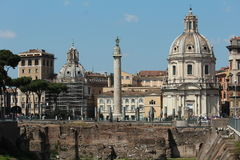Trajan's Column with italian landscape. Rome city center with traditional architecture and ambiance. A church to the right and Trajan's Column in the middle Stock Image