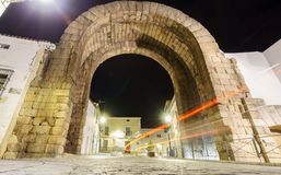 Trajano Arch at night with car light beam in Merida. Wide angle view of Trajano Arch at night with car light beam in Merida Stock Images