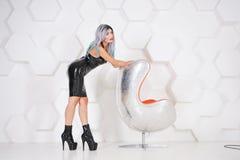 Traje alternativo de goma del látex de la mujer que lleva sexual caliente en fondo futurista del estudio blanco fotografía de archivo