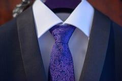 Traje con clase de los azules marinos con la camisa blanca y la corbata de seda bordada en el nudo de Windsor Imágenes de archivo libres de regalías