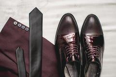 Traje, corbata, zapatos de cuero en una materia textil blanca Novios que se casan mañana Ciérrese para arriba de los accesorios d Imágenes de archivo libres de regalías