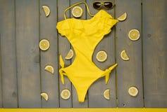 Traje de baño amarillo de una sola pieza, gafas de sol tipo aviador fotos de archivo libres de regalías