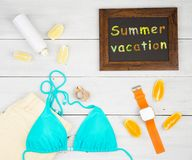 traje de baño azul, pantalones cortos amarillos, reloj elegante, protección solar, limón, naranja y pizarra con la inscripción y  Fotografía de archivo libre de regalías