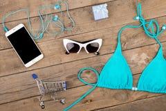 traje de baño azul, teléfono elegante, gafas de sol, auriculares, caja de regalo y carros de la compra en la tabla de madera marr Imagen de archivo libre de regalías