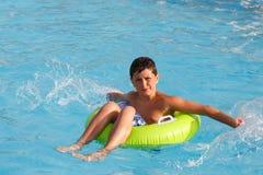 Traje de baño de los muchachos que flota en el flotador de la piscina Fotografía de archivo libre de regalías