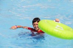 Traje de baño de los muchachos que flota en el flotador de la piscina Imagenes de archivo