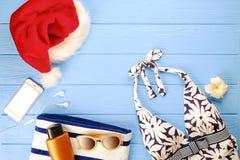 Traje de baño del ` s de la mujer y accesorio de la playa con la opinión superior del sombrero de Papá Noel, endecha plana, espac Fotografía de archivo